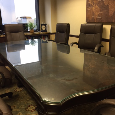 The dark brown wood boardroom table at Herman Law