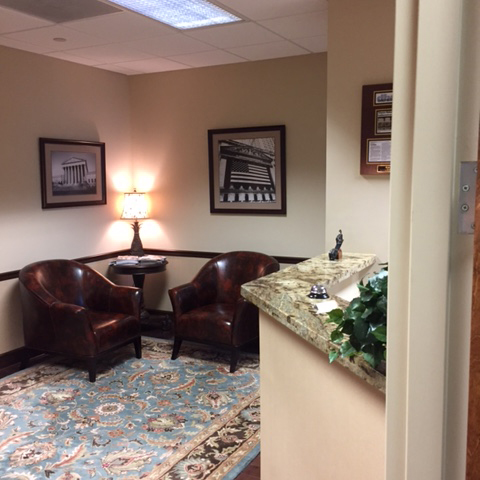 The reception waiting area at Herman Law with comfortable brown leather seats