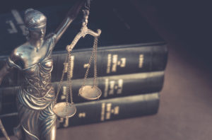 Law books and a statue of justice symbolizing fraud defense in West Palm Beach.