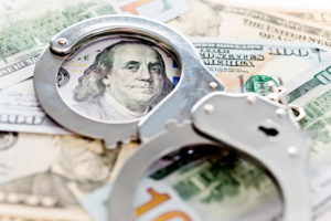 Handcuffs laying on top on American money symbolizing money laundering in West Palm Beach.