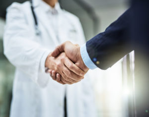 A handshake between a doctor and a patient. Patient Brokering in West Palm Beach.